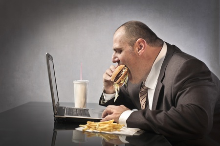 junk: Fat businessman eating junk food in front of a laptop