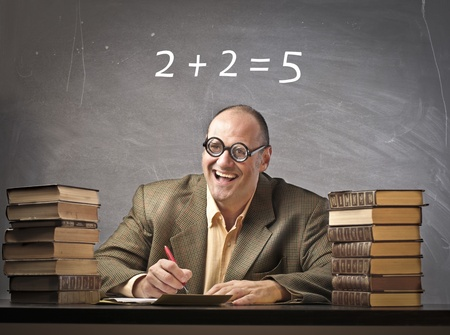 schoolmaster: Smiling teacher with wrong calculation on the blackboard in the background Stock Photo