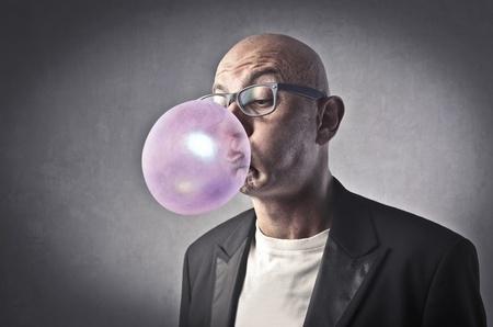 goma de mascar: Hombre que sopla burbujas con una goma de mascar