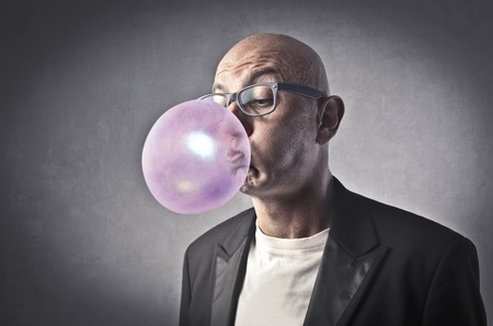 gums: Man blowing bubbles with a chewing gum Stock Photo