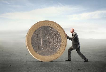 dinero euros: Hombre de negocios empujando un gigante de monedas de euro