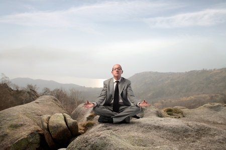 Businessman meditating in the mountains photo