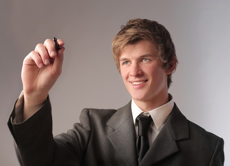 Smiling young businessman writing Stock Photo - 11571422