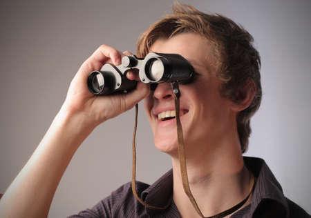Smiling young man using binoculars Stock Photo - 11571380