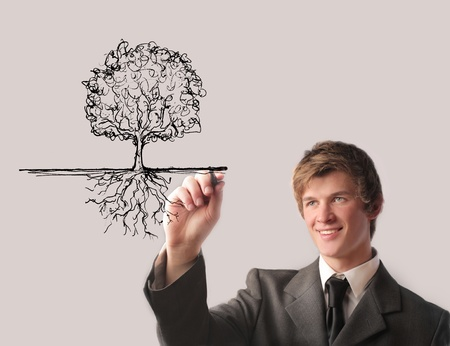 Smiling young businessman drawing a tree Stock Photo - 11571368
