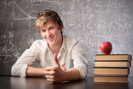 sybol: Smiling young student with thumbs up in a classroom Stock Photo