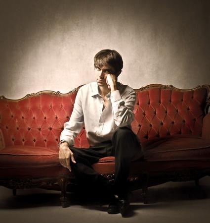 divan sofa: Handsome young man sitting on a velvet sofa