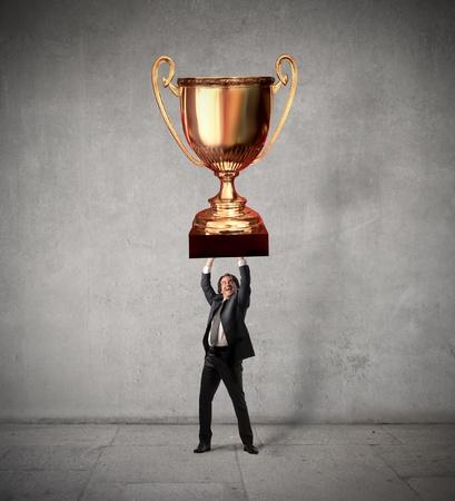 triumphing: Triumphing businessman raising a cup