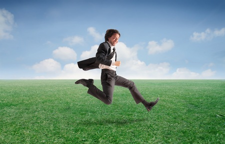sucess: Smiling businessman running on a green meadow
