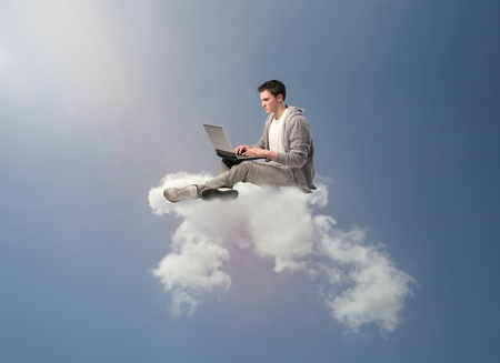 Young man sitting on a cloud and using a laptop photo