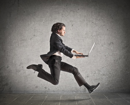 crazy man: Businessman running with a laptop in his hands Stock Photo