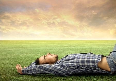 lying in grass: Joven de relax en un prado verde Foto de archivo