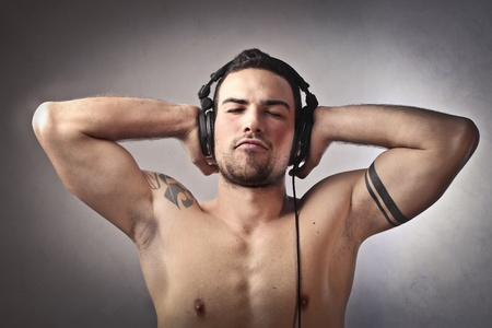 Young man enjoying music through headphones photo