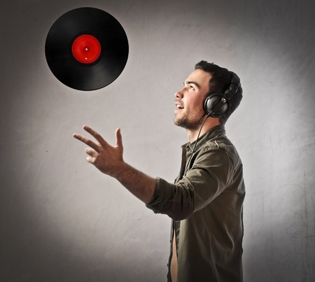 Disc jockey wearing headphones and throwing a disc in the air photo