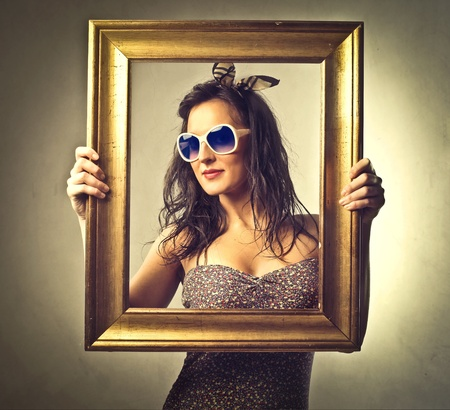 Beautiful woman holding an empty frame in front of her photo
