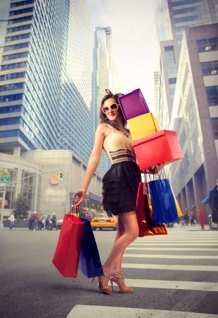美しい女性の都市通りに多くの買い物袋を運ぶ 写真素材