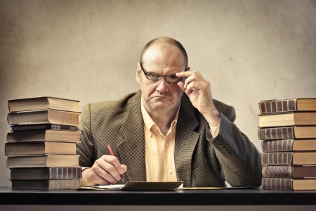 schoolmaster: Severe teacher surrounded by stacks of books and a calculator Stock Photo