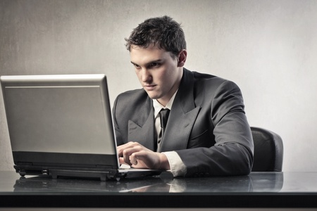 guy with laptop: Young businessman using a laptop