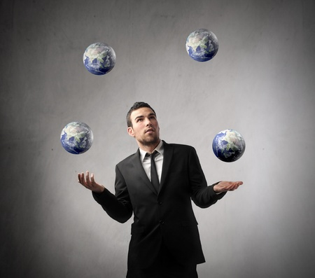 Young businessman juggling with earth planets photo