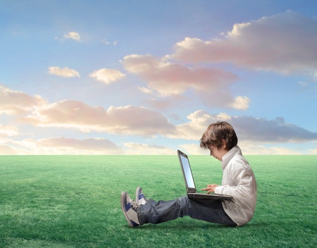 school computer: Child sitting on a green meadow and using a laptop