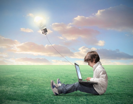 Child sitting on a green meadow and using a laptop with light bulb plugged in it photo