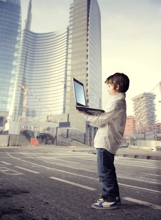Child holding a laptop on a city street photo