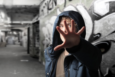 Young man hiding behind his hand on a city street photo