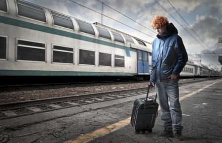 homme triste: Jeune homme portant une valise � roulettes sur le quai d'une gare de train Banque d'images