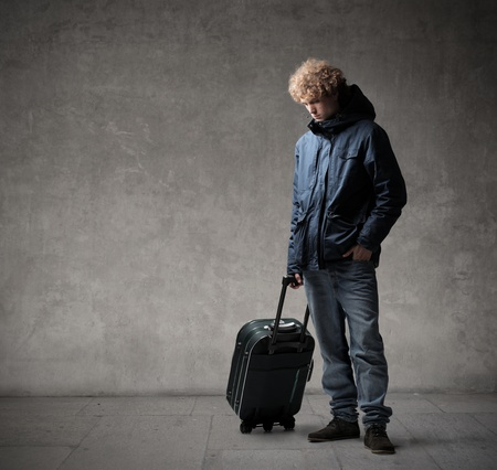 sad boy: Young man carrying a trolley case