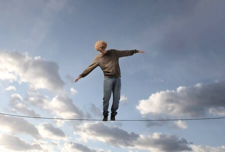 tightrope: Young man keeping his balance on a rope