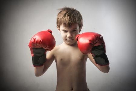 pugilist: Aggressive child wearing boxing gloves Stock Photo