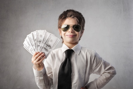 disguised: Smiling child disguised as a rich businessman holding many banknotes Stock Photo