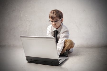 Child disguised as a businessman using a laptop photo