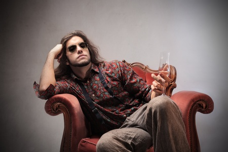 肘掛け椅子に座って、シャンパン グラスを保持している退屈の若い男