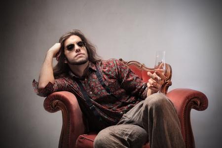 Bored jonge man zittend op een stoel en met een glas champagne