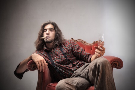 Bored young man sitting on an armchair and holding a glass of champagne and smoking a cigar photo