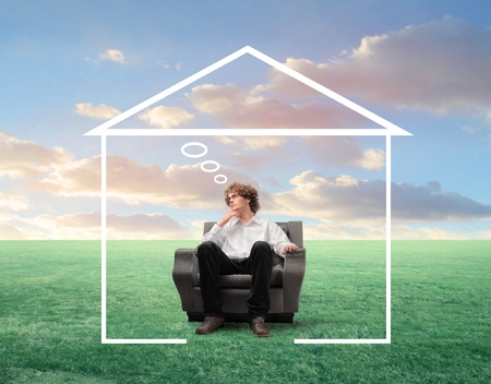 rural home: Young businessman with thoughtful expression sitting on an armchair on a green meadow and surrounded by the shape of a house