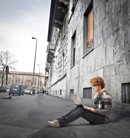 Young man sitting on a sidewalk and using a laptop photo