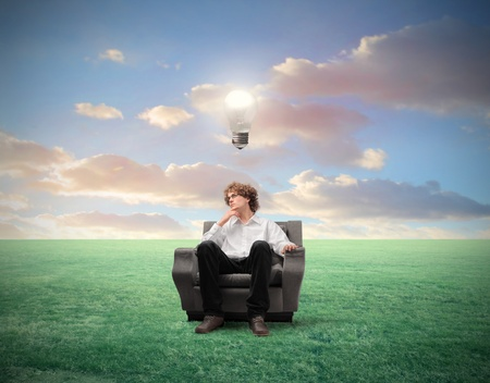 Young businessman sitting on an armchair on a green meadow with light bulb over his head photo