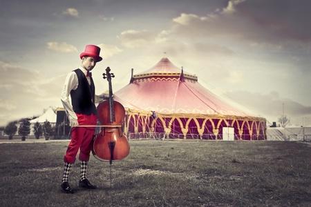 violoncello: Giovane uomo in abiti buffi in possesso di un violoncello con il circo in background Archivio Fotografico