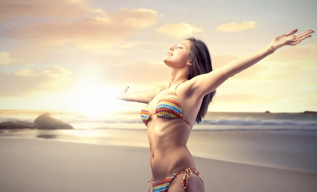 Beautiful woman stretching out her arms at the seaside photo