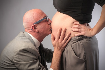 Man kissing his pregnant wifes belly photo