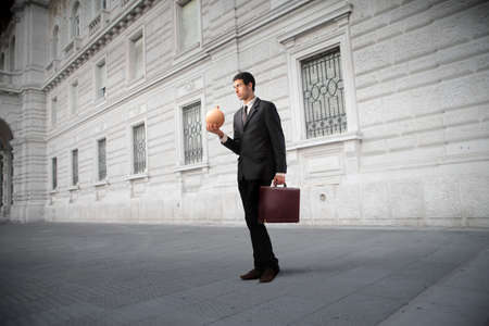 Businessman holding a money box with antique building in the background Stock Photo - 12199683