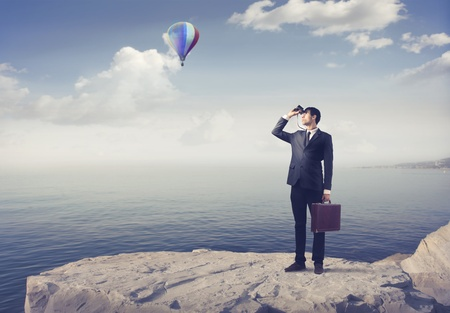 business briefcase: Businessman using binoculars with seascape and hot-air balloon in the background