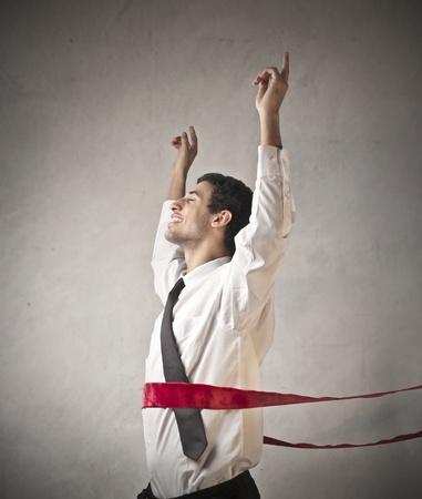 triumphing: Triumphing businessman crossing the line