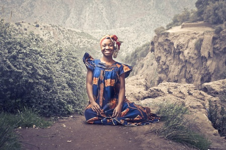 mujeres africanas: Mujer sonriente en traje tradicional africano que se sienta en una roca