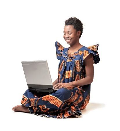 Smiling african woman in traditional dress using a laptop photo