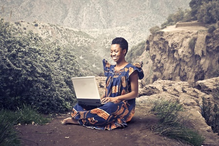 poor african: Smiling african woman in traditional dress sitting on a rock and using a laptop Stock Photo