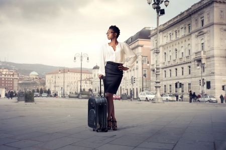 African businesswoman holding a trolley case on a city square Stock Photo - 12199692