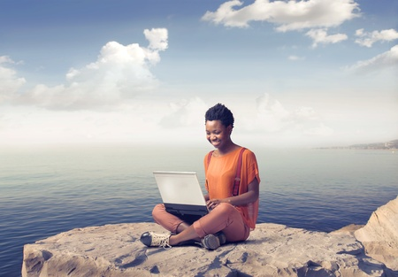 Smiling african woman sitting on a rock over the sea and using a laptop photo